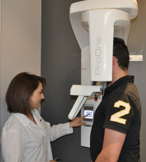 Dr. Tappuni gets ready to acquire a 					panoramic X-ray.